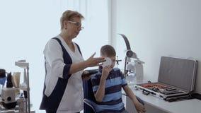 Cuide la vista de examen del ` s del muchacho con el marco de ensayo óptico almacen de metraje de vídeo