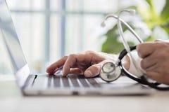 Cuide las notas pacientes que entran sobre el ordenador portátil en cirugía fotografía de archivo