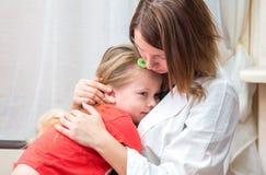 Cuide los abrazos y abrace a la pequeña muchacha enferma Imagen de archivo libre de regalías