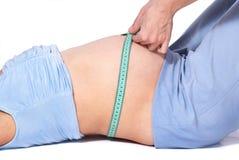 Cuide los brazos que miden longitud de la mujer embarazada de mentira del abdomen Imágenes de archivo libres de regalías