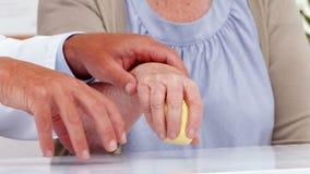 Cuide mostrando al paciente cómo ejercitar la mano herida almacen de metraje de vídeo