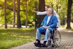 Cuide mostrar algo al hombre mayor en la silla de ruedas imagenes de archivo