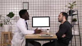Cuide mostrar informes médicos en su ordenador a su paciente, él está señalando en la pantalla Visualización blanca fotografía de archivo libre de regalías