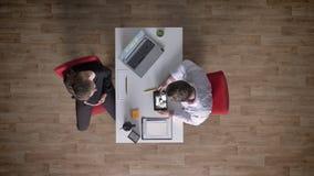 Cuide mostrar ultrasonido en la tableta a la mujer embarazada joven, sentándose en oficina, topshot, concepto médico almacen de metraje de vídeo