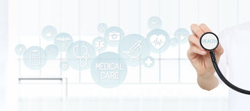 Cuide mostrar un estetoscopio en las manos con los iconos médicos Fotos de archivo libres de regalías