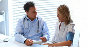 Cuide obrar recíprocamente con el paciente mientras que comprueba la presión arterial almacen de metraje de vídeo