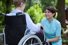 Cuide pasar tiempo con la mujer discapacitada en el parque Fotos de archivo