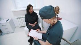 Cuide pedir la firma de un paciente en una recepción del hospital almacen de metraje de vídeo