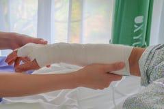 Cuide puesto el vendaje elástico para el brazo quebrado del paciente mayor Foto de archivo libre de regalías