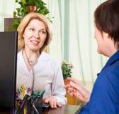 Cuide sentarse detrás del ordenador y hablar con el paciente foto de archivo libre de regalías