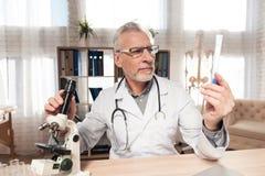 Cuide sentarse en el escritorio en oficina con el microscopio y el estetoscopio El hombre está sosteniendo el cubilete imágenes de archivo libres de regalías