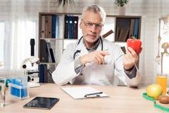 Cuide sentarse en el escritorio en oficina con el microscopio y el estetoscopio El hombre está sosteniendo la pimienta roja foto de archivo