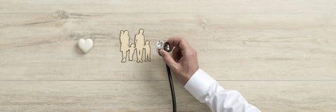 Cuide sostener el estetoscopio médico sobre cortado de una familia imagen de archivo libre de regalías