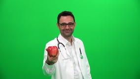 Cuide sostener una manzana contra una pantalla verde metrajes
