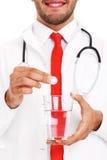 Cuide sostener una píldora y un vidrio de agua Imagenes de archivo