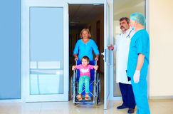 Cuide tomar cuidado del pequeño paciente en silla de ruedas en hospital Fotos de archivo