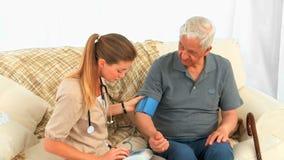 Cuide tomar la presión arterial de su paciente masculino almacen de video