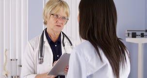 Cuide tomar notas sobre la tableta mientras que habla con el paciente Foto de archivo