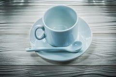 Cuillère à café blanche d'assiette creuse sur le conseil en bois photos stock