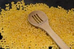 cuillère étroite sur des macaronis de pâtes Photo stock