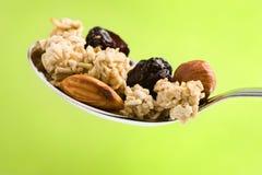 Cuillère avec de la céréale, les noix et le raisin sec Image libre de droits
