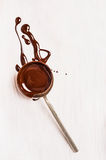 Cuillère avec du chocolat liquide sur en bois blanc Image libre de droits