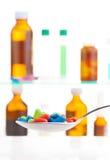 Cuillère avec les pilules de couleur et toute autre médecine Image libre de droits