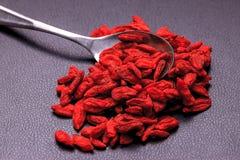 Cuillère dans une pile des wolfberries rouges Photographie stock libre de droits