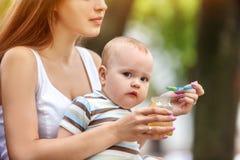 Cuillère de alimentation de bébé par la mère en parc extérieur sevrage Image stock
