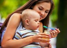 Cuillère de alimentation de bébé par la mère en parc extérieur sevrage Photographie stock