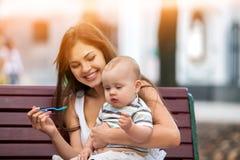 Cuillère de alimentation de bébé par la mère en parc extérieur Ton de couleur Image libre de droits