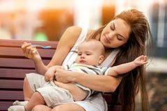 Cuillère de alimentation de bébé par la mère en parc extérieur Ton de couleur Image stock