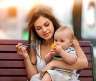 Cuillère de alimentation de bébé par la mère en parc extérieur Ton de couleur Photographie stock libre de droits