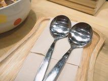 Cuillère de l'acier inoxydable deux placée sur les plats en bois image libre de droits