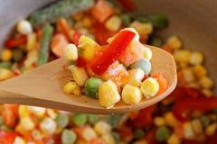 Cuillère de plan rapproché avec les légumes mélangés congelés Photo stock