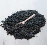 Cuillère des feuilles de thé vertes sèches sur le fond en bois Photographie stock libre de droits