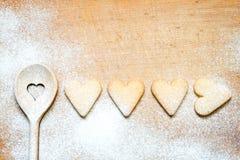 Cuillère en bois avec des biscuits faisant le fond cuire au four abstrait Photographie stock