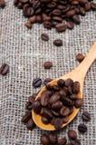 Cuillère en bois avec des grains de café Photos libres de droits