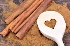Cuillère en bois avec les bâtons et la poudre de cannelle Photographie stock