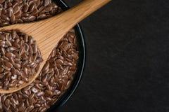 Cuill?re en bois dans le bol de graines de lin de Brown photographie stock