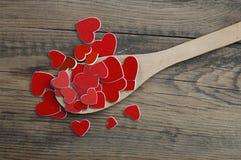 Cuillère en bois et beaucoup de coeurs Images stock
