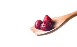Cuillère en bois et fraises d'isolement sur le blanc Photo stock