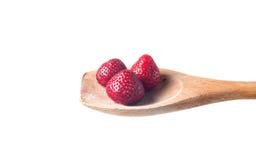 Cuillère en bois et fraises d'isolement sur le blanc Photo libre de droits