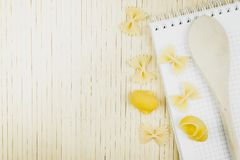 Cuillère en bois et papillon sec de nouilles sur une table en bois photos stock