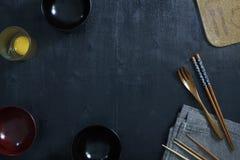 Cuillère en bois japonaise, baguettes, cuvette, oeufs crus frais et toile de table Photo libre de droits