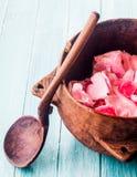 Cuillère en bois rustique par la cuvette remplie de Rose Petals Images stock