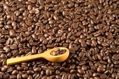 Cuillère en bois sur des grains de café Photos libres de droits