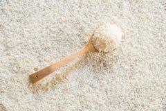 Cuillère en bois sur le fond de riz Image stock