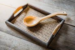 Cuillère en bois sur le plateau tissé par bambou chinois Photos stock