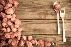Cuillère et fourchette au-dessus d'une table en bois avec les roses rouges, effet de vintage Image stock